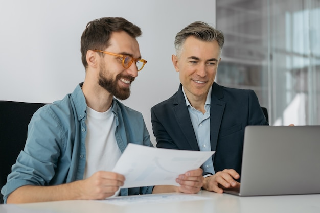 ラップトップコンピューターを使用し、スタートアップを計画し、オフィスで一緒に働くビジネスマン
