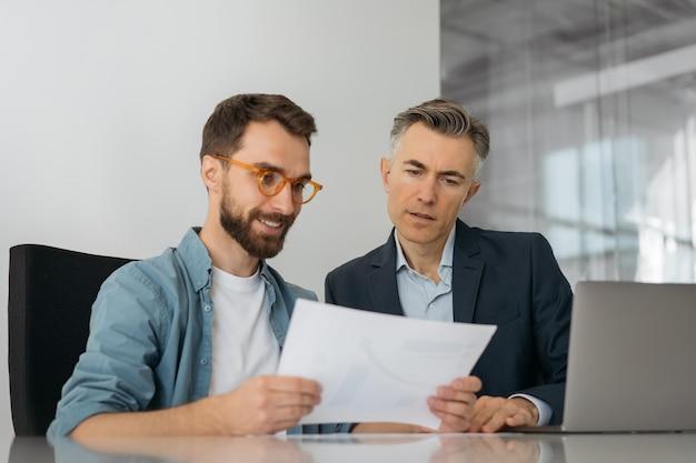 財務報告書の閲覧、統計の分析、スタートアップの計画、オフィスでの作業を使用するビジネスマン