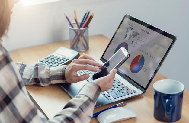 外国為替取引の株式金融と会計で働くスマートフォンとコンピューターを使用しているビジネスマン財務グラフの予算を分析し、事務室で将来の計画を立てます。