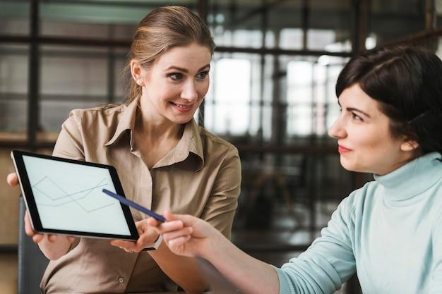 Persone di affari che utilizzano tablet durante una riunione al chiuso