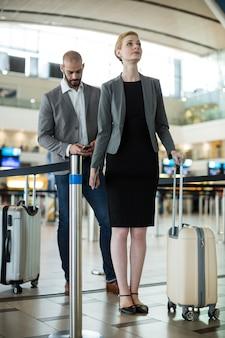 荷物を持ってチェックインカウンターで列に並んで待っているビジネスマン