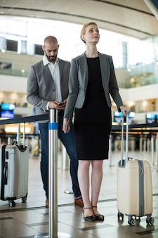 Businesspeople waiting in queue at a check-in counter with luggage