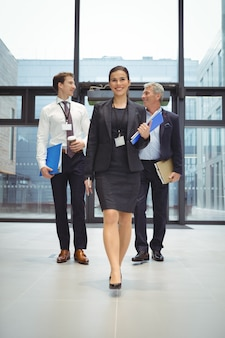 Businesspeople walking together with file