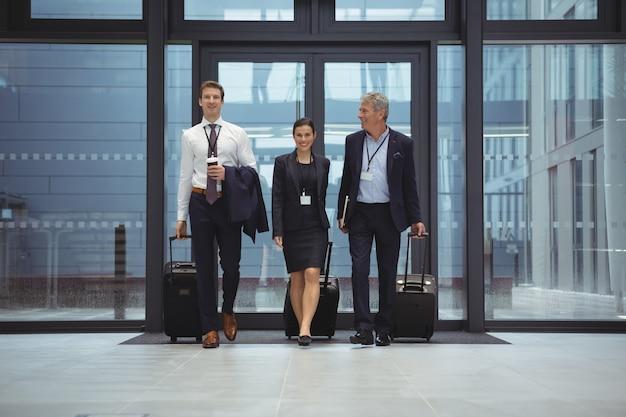 Бизнесмены, идущие вместе с багажом