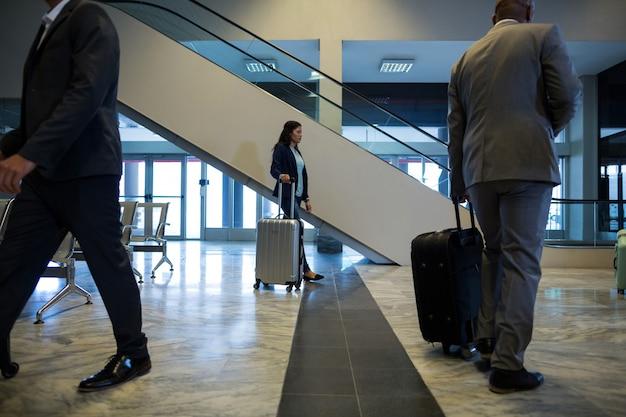 待合室で荷物を持って歩くビジネスマン