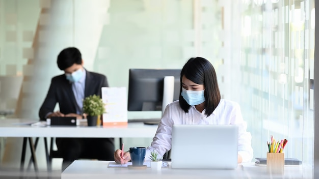 Businesspeople wearing protective mask working in modern office.
