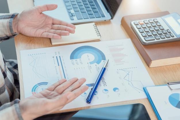 財務および会計で働くビジネスマンは、オフィスルームで財務グラフの予算と将来の計画を分析します。