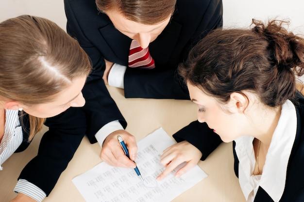 Businesspeople working on spreadsheet