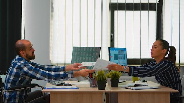 テクノロジーを変えるドキュメントを使用して金融企業の建物で一緒に働くビジネスマン、車椅子に固定されて座っているビジネスマン。グラフを分析する障害者障害者起業家