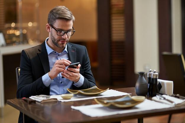 Бизнесмен в элегантной одежде нажимает пальцами на черный дисплей мобильного телефона, сидя за столом с пустыми тарелками
