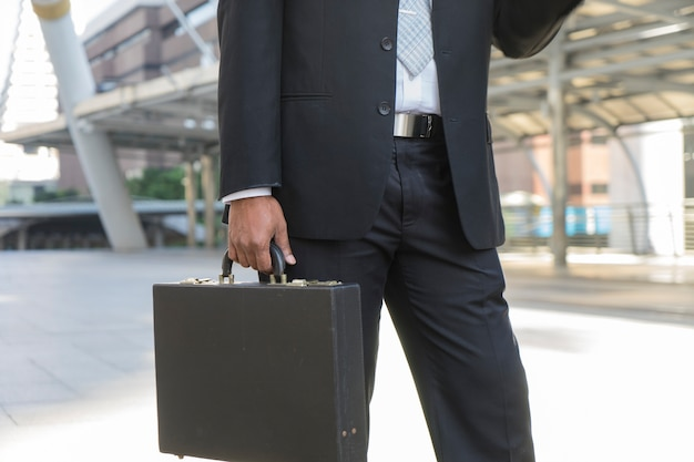 Businessperson is carrying his briefcase and heading for work.