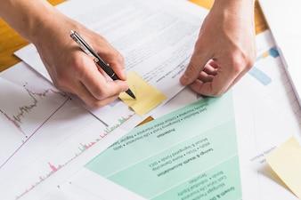 文書の上に付箋紙の印をつけるビジネスマンの手
