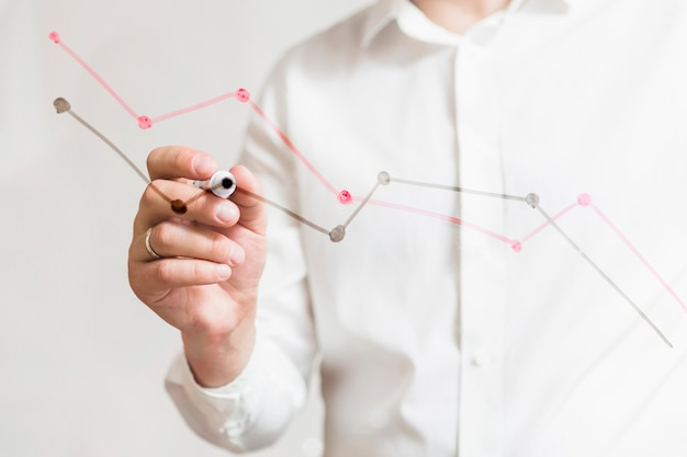 Businessperson's hand preparing graphs on glass board with marker