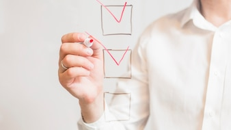 Businessperson's hand ticking off check boxes with red marker on screen