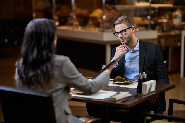 タブレットを向ける女性と彼のあごをなでるビジネスマン