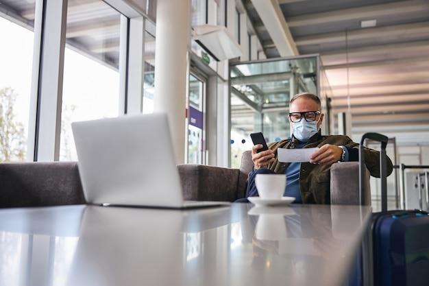 Бизнесмен с мобильным телефоном, сидя в кресле