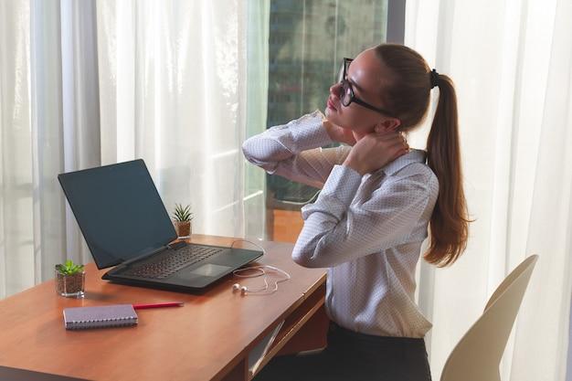 Предприниматель в очках испытывает боли в мышцах шеи и массирует место дискомфорта. сидячая работа. нужен отдых