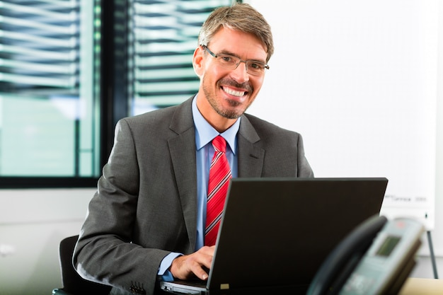 Бизнесмен с ноутбуком в своем офисе