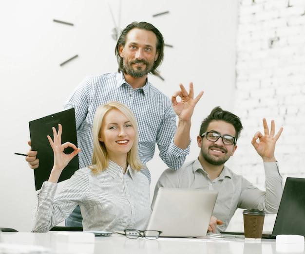 Улыбающийся businessteam показывает ok жесты в офисе