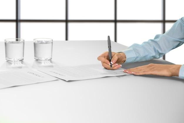 実業家の手署名文書。女性のサインはデスクで契約します。白い背景の上の雇用手順。すべてを考え直してください。