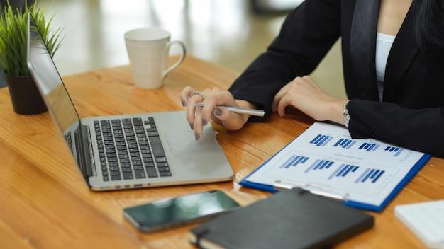 Бизнесвумен анализирует финансовую деятельность компании через ноутбук с финансовым отчетом