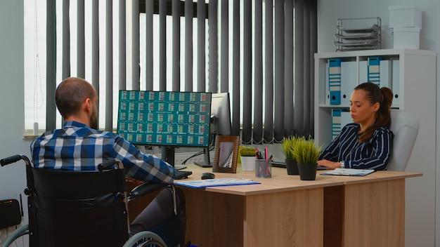 ビルのオフィスの机の上の車椅子チェックグラフに座っている障害者の同僚と話している財務統計を分析する実業家。現代の技術を使用して障害のあるビジネスマン
