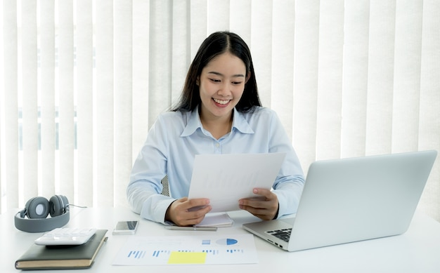 Businesswoman analysis the chart and meeting video conferencing with laptop at the home office for setting challenging business goals and planning to achieve the new target.