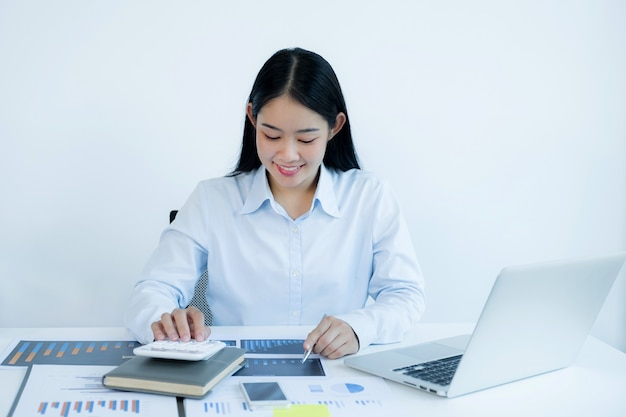 Businesswoman analysis the chart with laptop at home office for setting challenging business goals