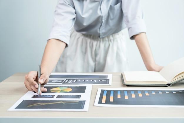 Деловая женщина анализирует диаграмму с ноутбуком в офисе для постановки сложных бизнес-целей и планирования для достижения новой цели.