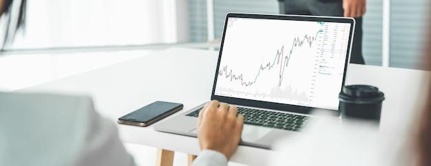 Businesswoman in analyze stock market data using laptop computer proficiently