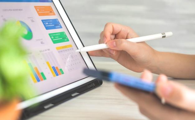 무선 스타일러스 펜을 사용하여 디지털 태블릿에서 회사 성과를 분석하는 사업가입니다. 화면의 비즈니스 및 재무 다이어그램, 손에 스마트폰이 있는 사무실 책상 사진