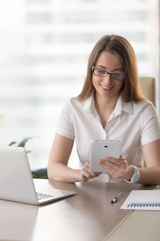 Businesswoman analyzing statements on tablet