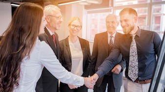 Businesswoman and businessman shaking each other's hand in the meeting