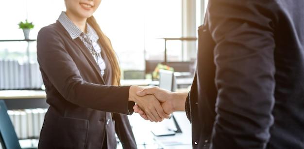 계약서에 서명한 후 사무실 배경에서 악수하는 사업가와 사업가, 또는 악수 인사말 거래, 비즈니스는 자신감을 대담하고 성공적인 개념을 표현했습니다.