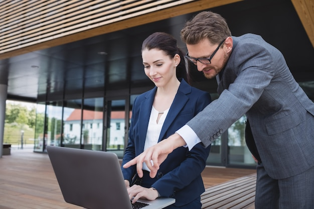 Деловая женщина и коллега, используя ноутбук