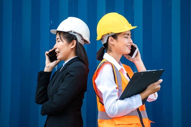 コンテナの前で電話で話している実業家と工場労働者