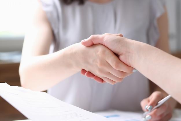 Деловая женщина и женщина пожимают друг другу руки в офисе