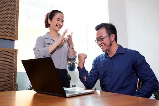 同僚を拍手する実業家