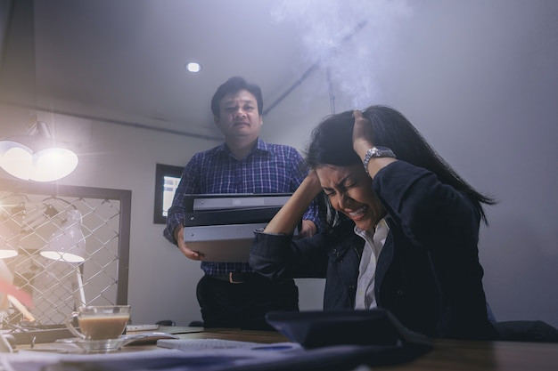 Businesswoman are stressed after receiving many jobs from colleague on overtime working.