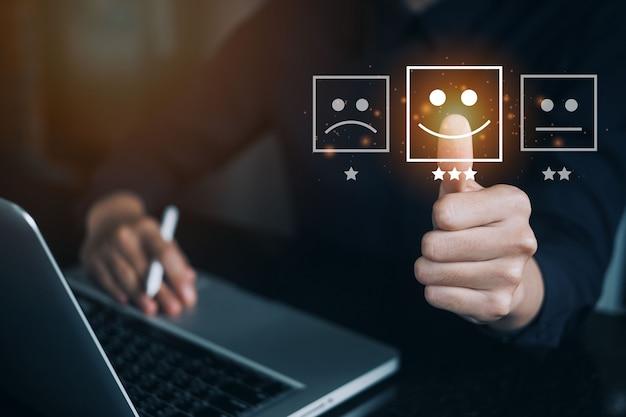 사업가는 행복한 웃는 얼굴 아이콘의 가상 화면을 만지고 노트북 컴퓨터로 서비스에 만족을 주고 있습니다. 고객 서비스 및 만족 개념