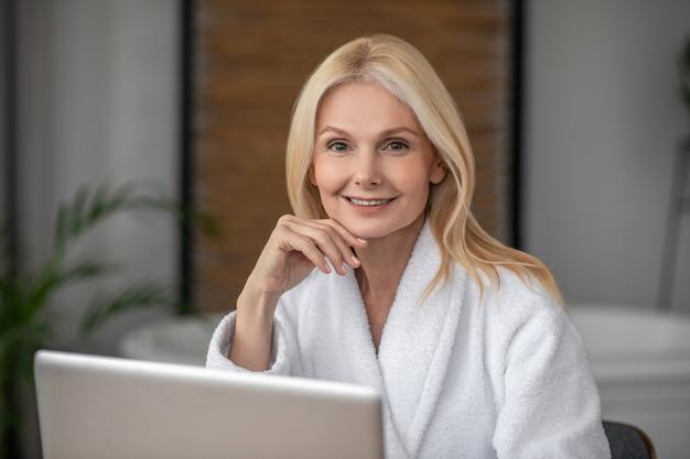 自宅で実業家。ラップトップと白いバスローブの美しいブロンドの女性