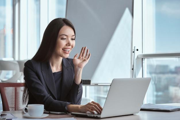 Деловая женщина в офисе одна сидит за столом с чашкой горячего кофе, имея видеозвонок на ноутбуке, машет в камеру, улыбаясь веселым