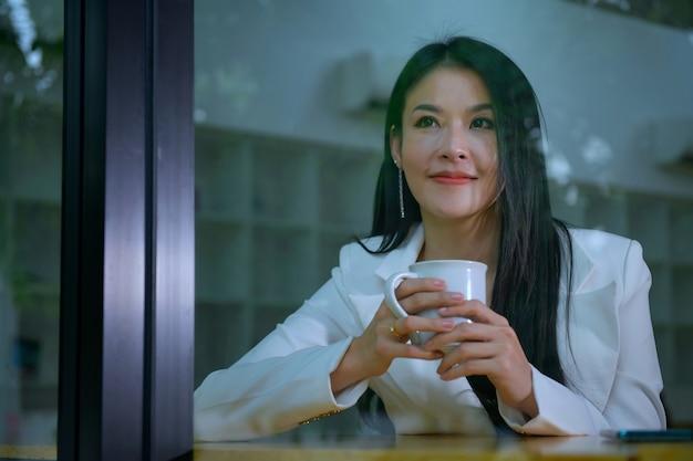 휴식을 취하기 위해 점심 시간에 커피를 마시는 아름다운 여성, 비즈니스 개념