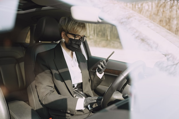 Businesswoman in a black mask sitting inside a car