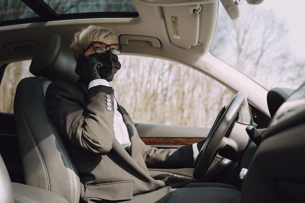Donna di affari in una maschera nera che si siede dentro un'automobile