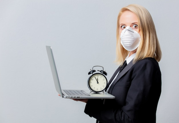 Businesswoman in black suit and face mask with alarm clock and computer