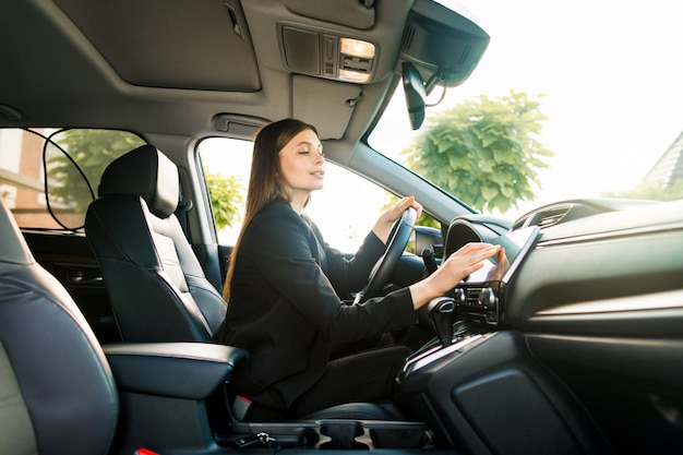 Businesswoman in black suit sits behind the wheel of a premium car and looks the way looking at the monitor of navigation system