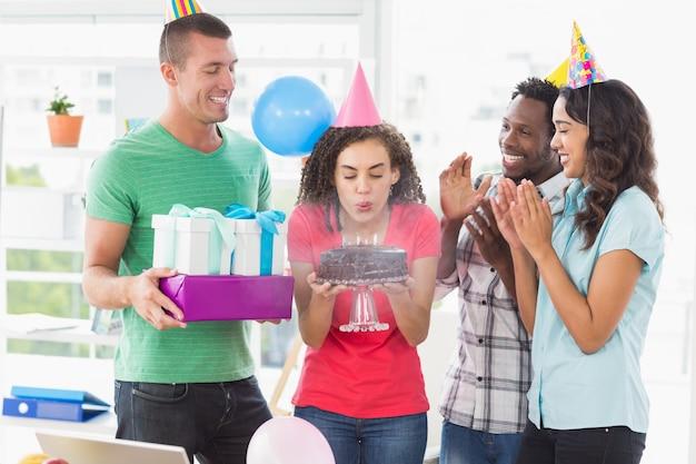 彼女の誕生日のケーキにキャンドルを吹くビジネスマン