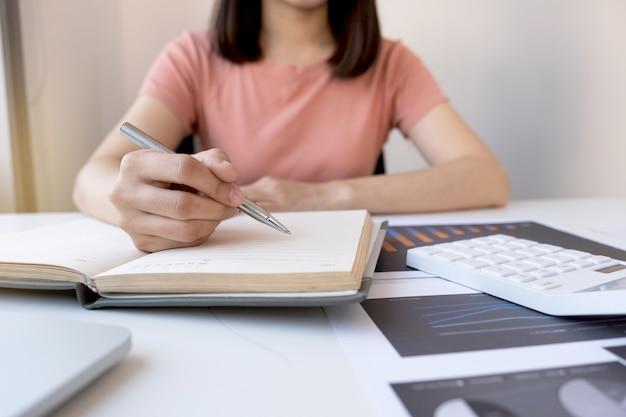 Деловая женщина бухгалтер отмечает анализ графика с калькулятором и ноутбуком в домашнем офисе