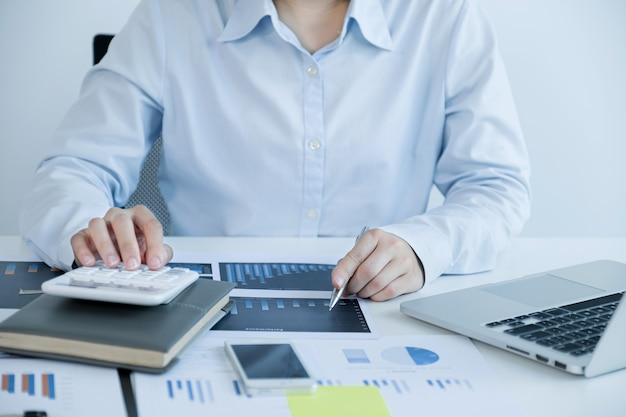 Businesswoman bookkeeper holding pen, use calculator and laptop doing account for paying tax